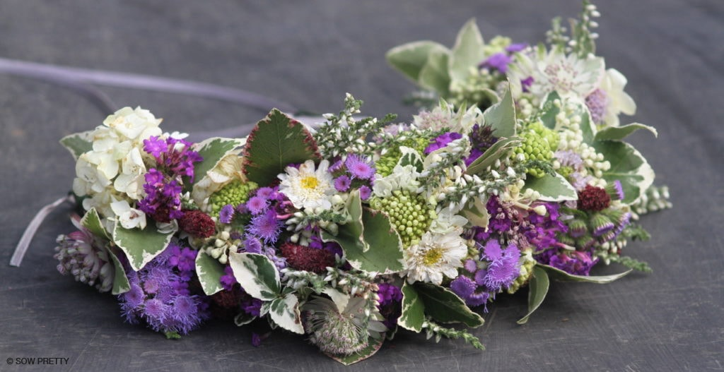 A crown of purple, maroon and cream flowers